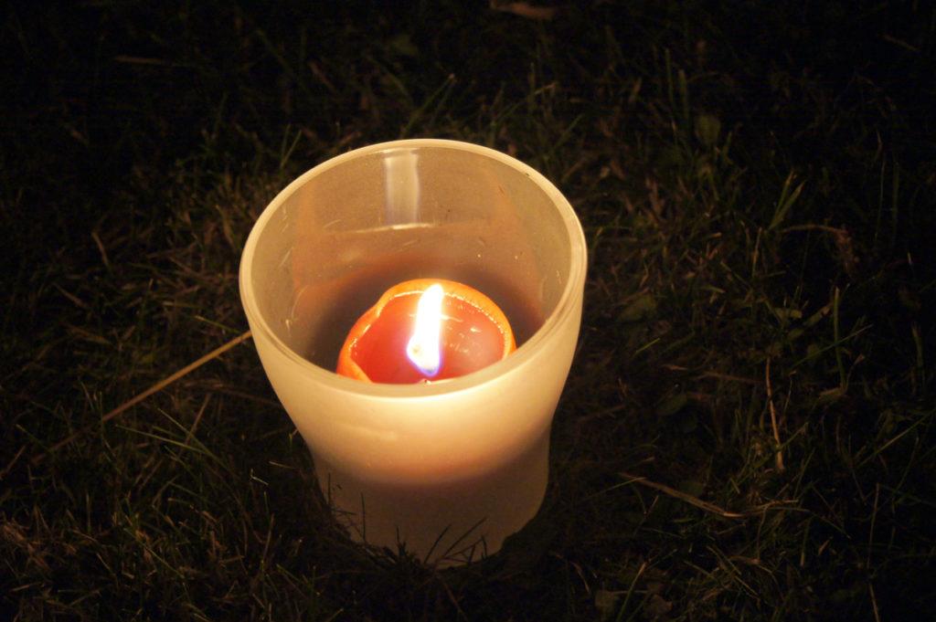 Kerze in einem Glas auf Rasen